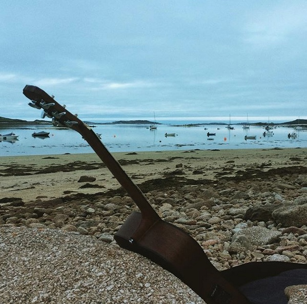 An acoustic guitar on the beach on the island of Bryher during a songwriting session