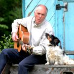 Singer, songwriter and author Terence Blacker with his guitar and his dog looking like they're singing together